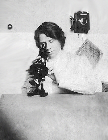 "Mariam Vinograd-Villchur with a microscope. The title of the slim book hanging under the telephone is ""New York City Telephone Directory."""